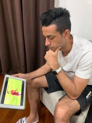 Melalui gawai miliknya, bek Persija Jakarta, Otavio Dutra menyaksikan pertandingan uji coba Timnas U23 Indonesia melawan Tira Persikabo yang berakhir 2-0 di Stadion Madya Jakarta, Jumat (05/03/2021) malam.