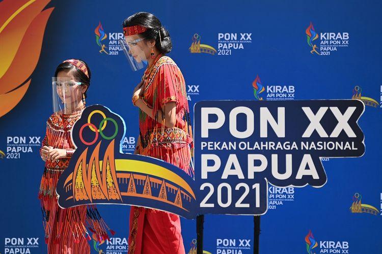 Dua warga melintas di dekat pernak-pernik <a href='https://manado.tribunnews.com/tag/pon-papua' title='PONPapua'>PONPapua</a> di kawasan Pasar Lama Timika, Kabupaten Mimika, Papua, Selasa (28/9/2021). Berbagai pernak-pernik <a href='https://manado.tribunnews.com/tag/pon-papua' title='PONPapua'>PONPapua</a> terpasang di sejumlah titik di Timika untuk memeriahkan pagelaran olah raga nasional empat tahunan tersebut.  ANTARA FOTO/Aditya Pradana Putra/tom.