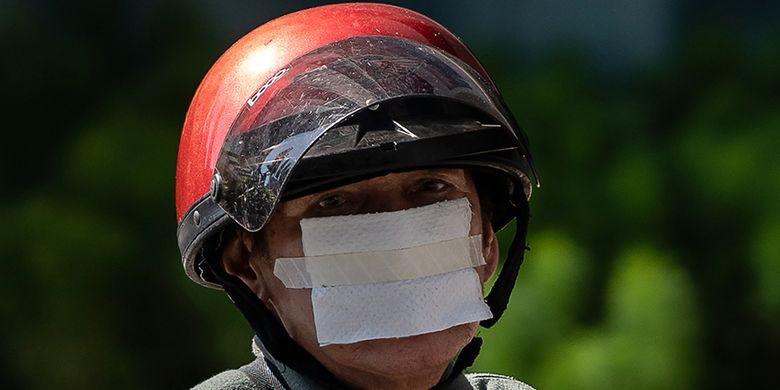 Seorang pria mengenakan lembaran tisu yang diplester sebagai pengganti masker untuk pencegahan terhadap penyebaran virus corona (Covid-19), di Kuala Lumpur, Malaysia, Rabu (25/3/2020).