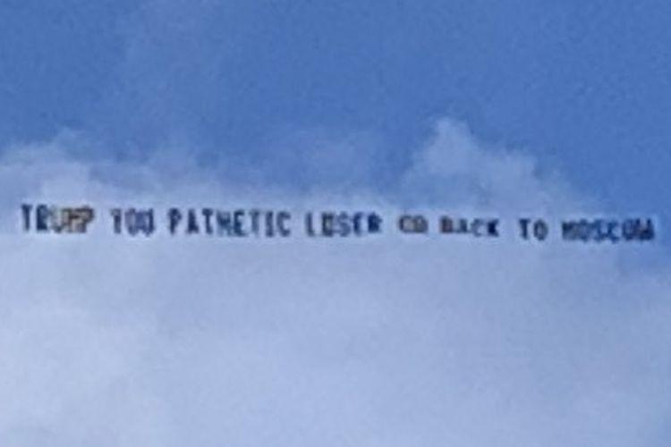 Spanduk yang ditarik dengan pesawat kecil melintasi langit itu berbunyi: Trump, kamu pecundang yang menyedihkan kembali ke Moskwa.