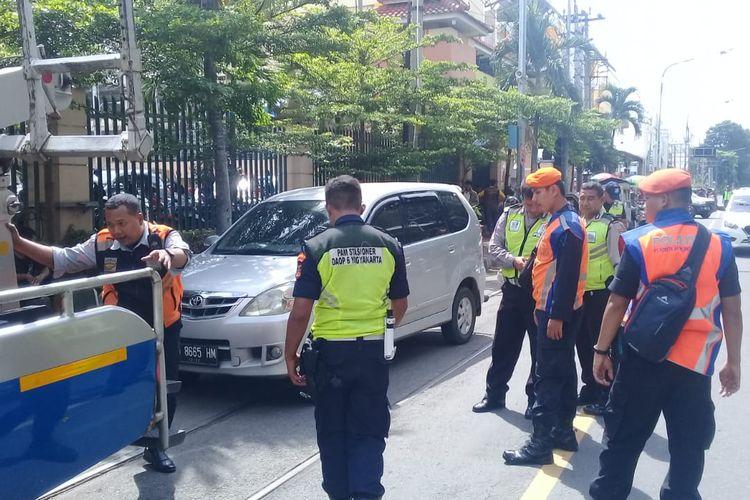 Sejumlah petugas menderek mobil Toyota Avanza yang nekat parkir di atas perlintasan kereta api di jalan Mayor Sunaryo, Solo, Jawa Tengah.