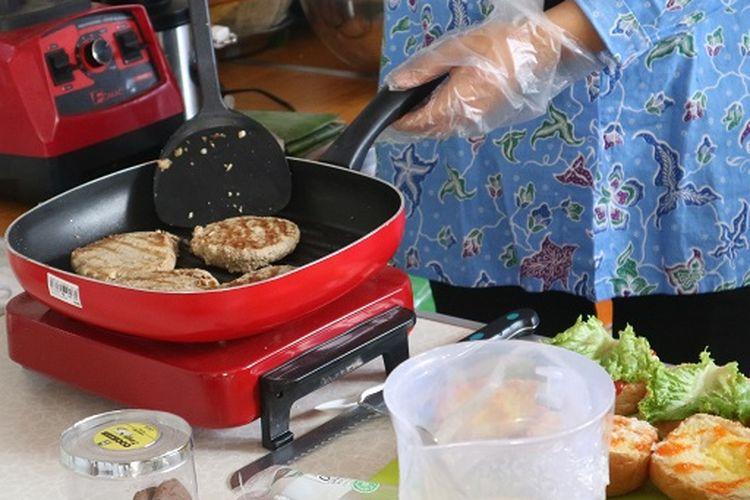 Proses memasak patty dari burger tempe. Parry yang digoreng berbahan tempel.