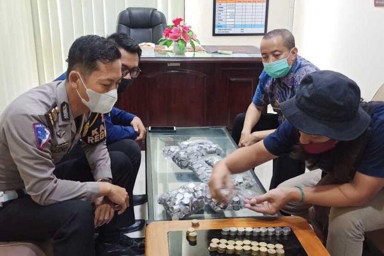 BAYAR PAJAK-- Nursam Romdoni, pedagang mainan dan aksesoris wanita asal Kelurahan Kertosari, Kecamatan Ponogoro, Kabupaten Ponorogo membayar pajak mobil dengan uang koin yang dikumpulkan dalam setahun.