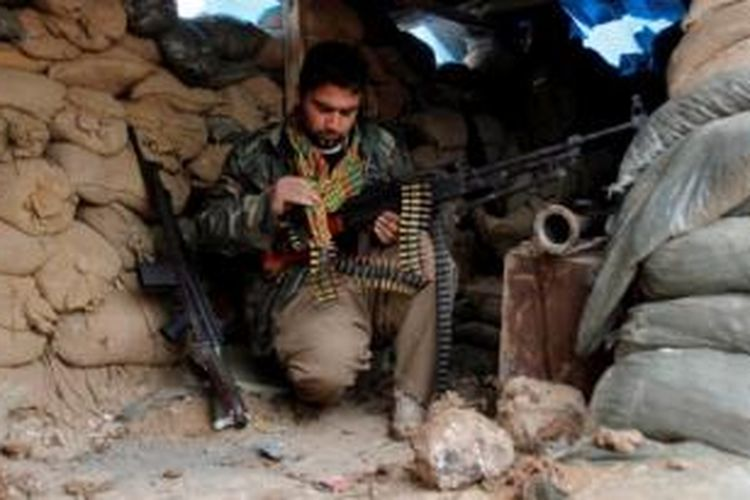 Seorang pejuang Peshmerga Kurdi tengah memeriksa senjatanya di sela-sela pertempuran melawan ISIS di Kirkuk, Irak.