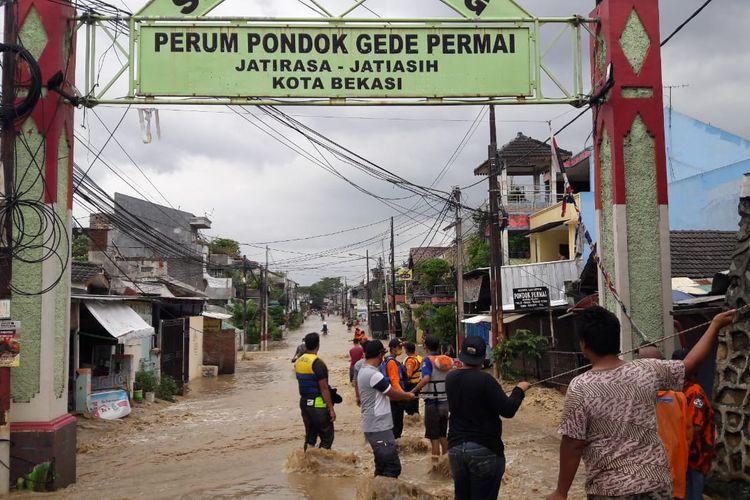 Tali tambang dibentangkan untuk mengevakuasi warga Pondok Gede Permai di tengah derasnya arus banjir pada Jumat (19/2/2021).