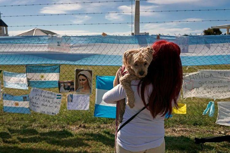 Salah seorang warga melihat deretan pesan dukungan kepada awak kapal selam Argentina yang hilang sejak pekan lalu.