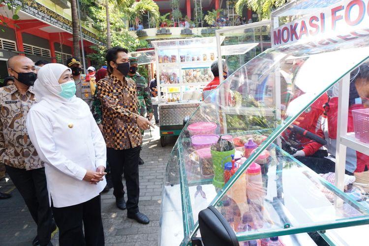 MOKASI—Gubernur Jawa Timur, Khofifah Indarparawansa bersama Bupati Madiun, Ahmad Dawami melihat mobil listrik kampung pesilat besutan anak-anak SMK Model PGRI I Mejayan beberapa waktu lalu.