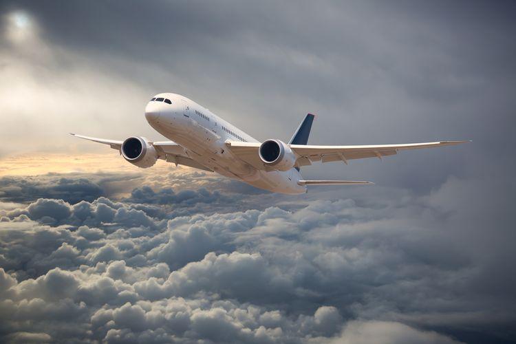 Ilustrasi pesawat terbang di tengah cuaca mendung dan awan cumulonimbus.