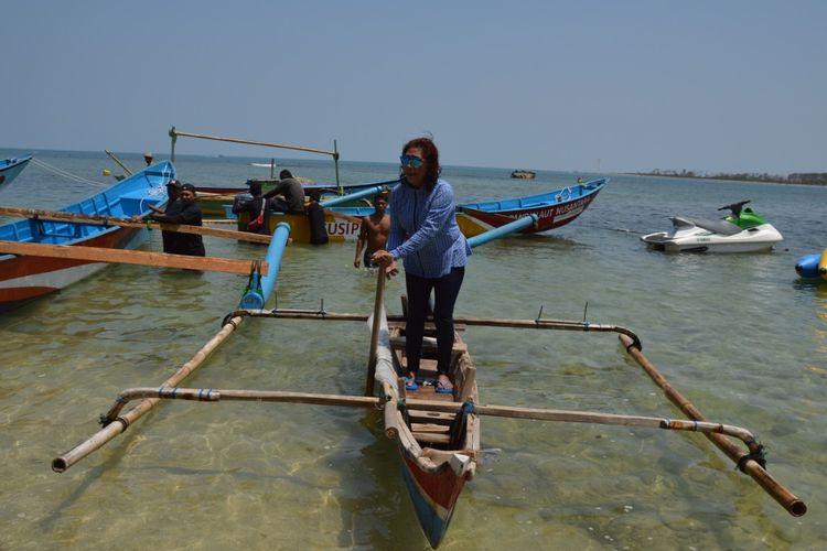 Susi Pudjiastuti dengan perahu dayung milik Mulyani, nelayan Pandeglang yang mendapat perahu dari metode tukar guling dengan perahu baru.