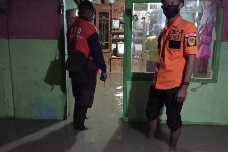 Salah satu petugas tim BPBD Kabupaten Madiun turun ke lokasi banjir di Desa Klumutan, Kecamatan Saradan setelah hujan mengguyur empat jam di daerah tersebut.
