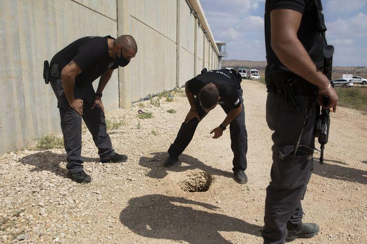 Polisi dan sipir penjara memeriksa lokasi pelarian enam milisi Palestina di luar Penjara Gilboa di utara Israel, Senin, 6 September 2021. Pasukan israel menggelar pencarian setelah para tahanan kabur dari lubang yang digali di toilet.