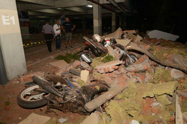 Warga melihat kendaraan yang hancur tertimpa puing bangunan yang runtuh akibat gempa, di salah satu mall, di Denpasar, Minggu (5/8/2018). Gempa yang mengguncang Lombok, Nusa Tenggara Barat, juga terasa hingga Bali.