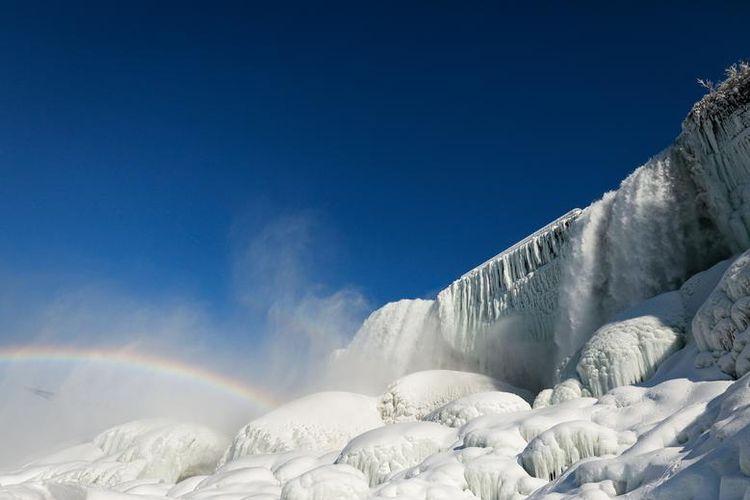 Pemandangan air yang mengalir di antara es yang membeku di Air Terjun Niagara yang terlihat dari bawah air terjun, New York, Amerika Serikat (dok. REUTERS/Lindsay DeDario).