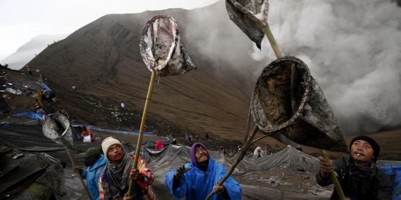 Beberapa warga Suku Tengger mencoba menangkap sesaji yang dilemparkan ke dalam Kawah Bromo oleh penganut Hindu Tengger, saat Yadnya Kasada digelar pada 20-21 Juli 2016.