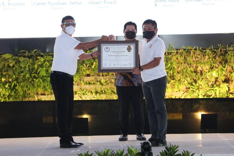 Menteri BUMN RI Erick Thohir (tengah) menyaksikan penyerahan sertifikat apresiasi 25 tahun Telkom tercatat dan diperdagangkan di Bursa Efek Indonesia yang diserahkan langsung oleh Direktur Utama Bursa Efek Indonesia Inarno Djajadi (kiri) kepada Direktur Utama Telkom Ririek Adriansyah (kanan) di Jakarta, Kamis (19/11).