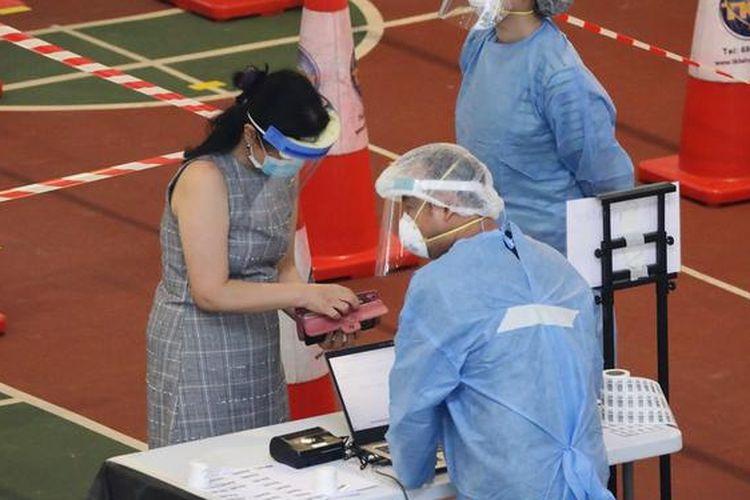 Seorang warga Singapura mendaftarkan diri untuk menjalani tes swab di pusat pengujian Covid-19.