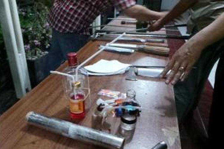 Aparat Polres Jakarta Pusat menunjukkan barang bukti yang disita dalam penangkapan mahasiswa Universitas Kristen Indonesia (UKI) Salemba, Rabu (7/8/2013) malam. Para mahasiswa itu diduga melakukan penyerangan terhadap petugas keamanan Rumah Sakit Cipto Mangunkusumo.