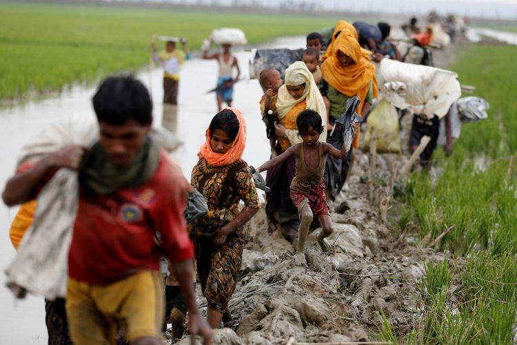 Pengungsi Rohingya berjalan di jalan berlumpur setelah menyeberangi perbatasan Banglades-Myanmar di Teknaf, Banglades, Minggu (3/9/2017).