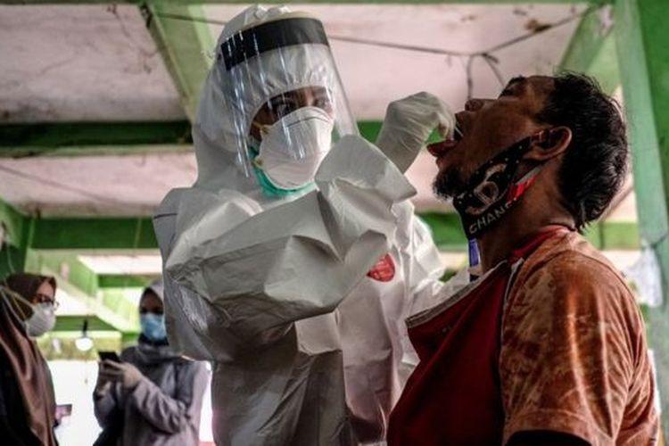 Petugas mengambil sampel cairan dari hidung dan tenggorokan pedagang saat mengikuti swab test di Pasar Pagi, Kota Pangkalpinang, Kepulauan Bangka Belitung, Kamis (11/06).