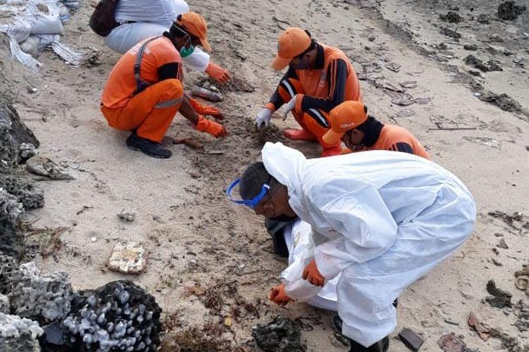 Petugas dari Pertamina dibantu PPSU Kepulauan Seribu mengumpulkan gumpalan minyak di sekitar Pulau Pari, Kepulauan Seribu, Rabu (12/8/2020)