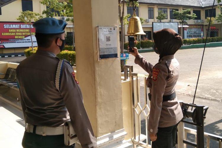 Salah satu personel Polda Lampung memindai kode bar aplikasi PeduliLindungi sebelum masuk area Mapolda Lampung.
