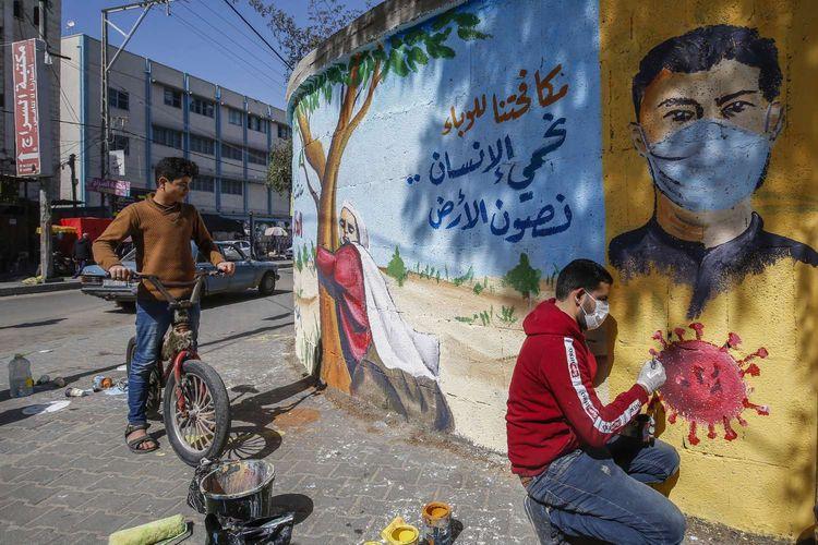 Seniman mural Palestina membuat pesan melawan virus corona di Rafah, Selatan Jalur Gaza, 29 Maret 2020. Pandemi Covid-19 yang disebabkan oleh virus corona menjadi insipirasi seniman grafiti untuk memberikan peringatan dan motivasi bagi warga dalam menghadapi virus tersebut.