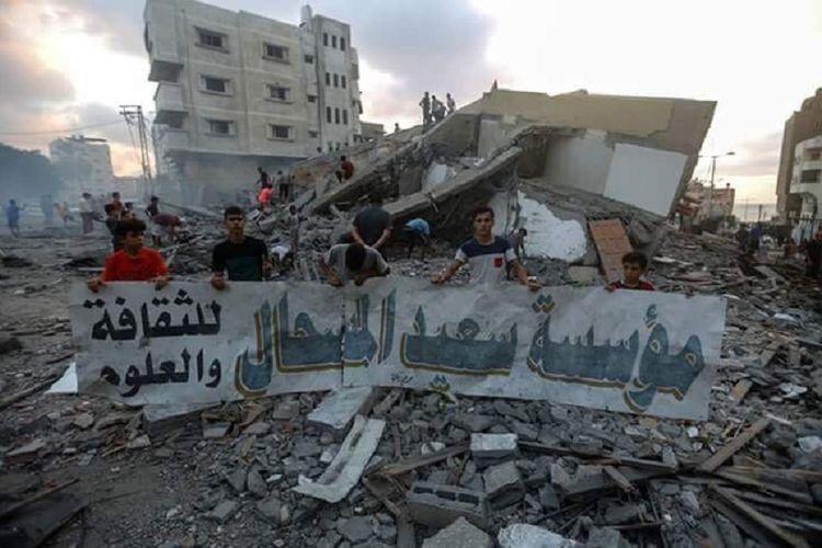 Warga Gaza memegang tanda Pusat Kebudayaan Al-Meshaal. Bangunan tersebut dilaporkan hancur dalam serangan udara yang dilakukan Israel Kamis (9/8/2018).