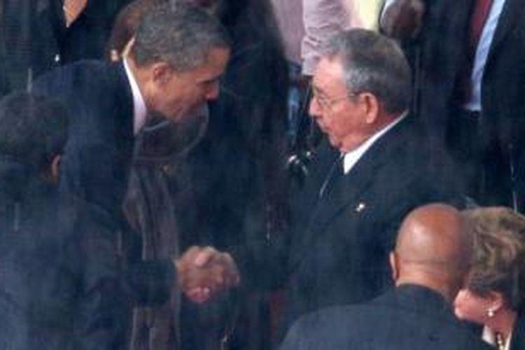 Presiden Barack Obama menjabat tangan presiden Kuba, Raul Castro saat keduanya menghadiri upacara kebaktian mengenang Nelson Mandela, di Soweto, Selasa (10/12/2013).