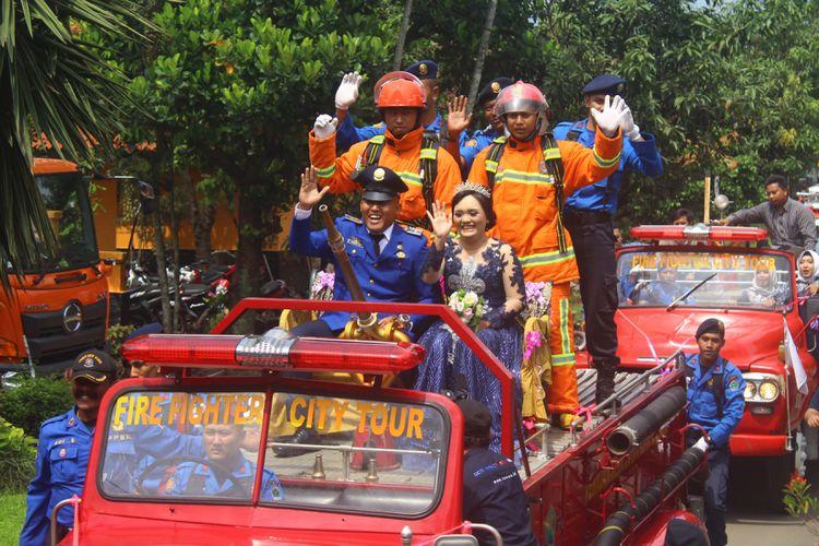 Salah satu anggota UPT Pemadam Kebakaran Kota Malang saat diarak keliling kota menggunakan mobil pemadam kebakaran bersama mempelai wanitanya, Sabtu (8/12/2018). Arak - arakan itu merupakan tradisi di lingkungan UPT Pemadam Kebakaran Kota Malang bagi anggotanya yang sedang melangsungkan resepsi pernikahan.