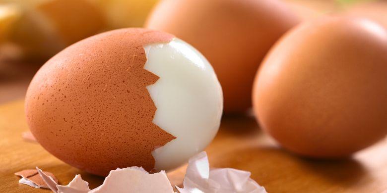Ilustrasi telur rebus yang telah dikupas cangkangnya sebagian.