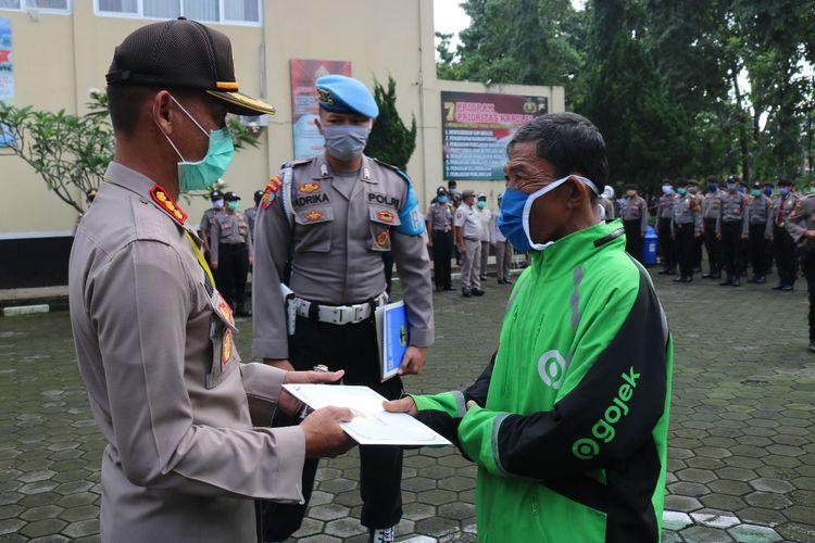 Kapolresta Banyumas Kombes Whisnu Caraka memberikan santunan kepada Mulyono, pengemudi ojol yang menjadi korban penipuan di halaman Mapolresta Banyumas, Jawa Tengah, Selasa (7/4/2020).