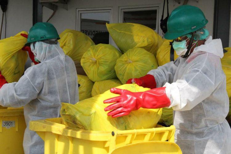 Petugas dari PT Jasa Medivest tengah mengangkut limbah medis.