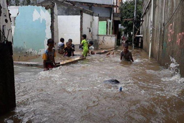 Sejumlah anak-anak tengah bermain di tengah banjir yang melanda Pemukiman di RT 001/03 Cipinang Melayu, Makasar, Jakarta Timur pada Selasa (16/2/2021).