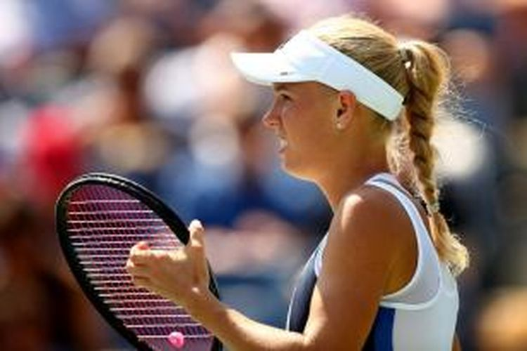 Petenis Denmark, Caroline Wozniacki, menarik senar raketnya saat menghadapi Duan Ying-ying dari China, pada babak pertama US Open, di Billie Jean King National Tennis Center, New York, Selasa (27/8/2013).