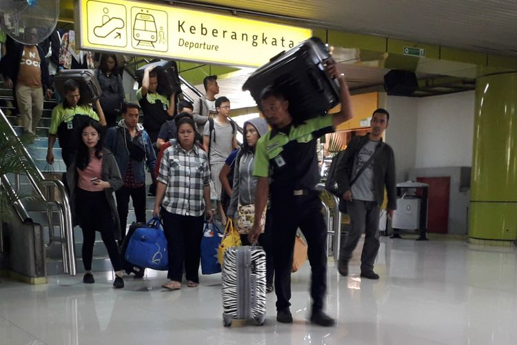 Seorang porter tengah membawa koper milik penumpang di Stasiun Gambir, Jakarta Pusat, Sabtu (9/6/2018).