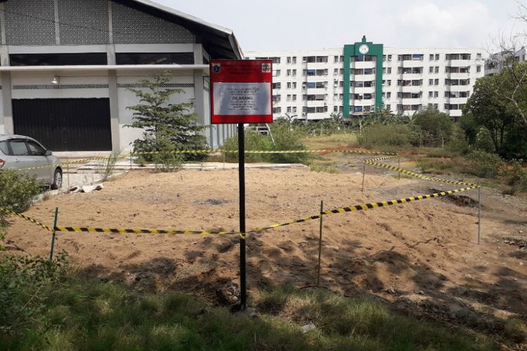 Papan peringatan dipasang di area temuan gundukan tamah diduga limbah B3 di Marunda, Jakarta Utara, Rabu (9/1/2019).
