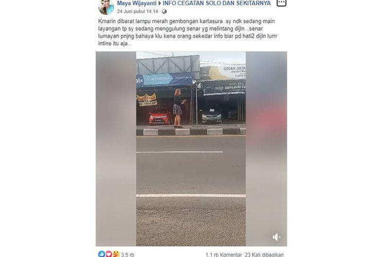 Tangkapan layar video seorang wanita tengah menggulung senar layangan yang melintang di tengah jalan.