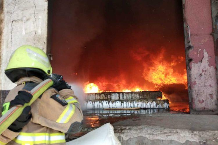 Tampak petugas tengah berupaya memadamkan api yang membakar gudang kasur di Cimahi.