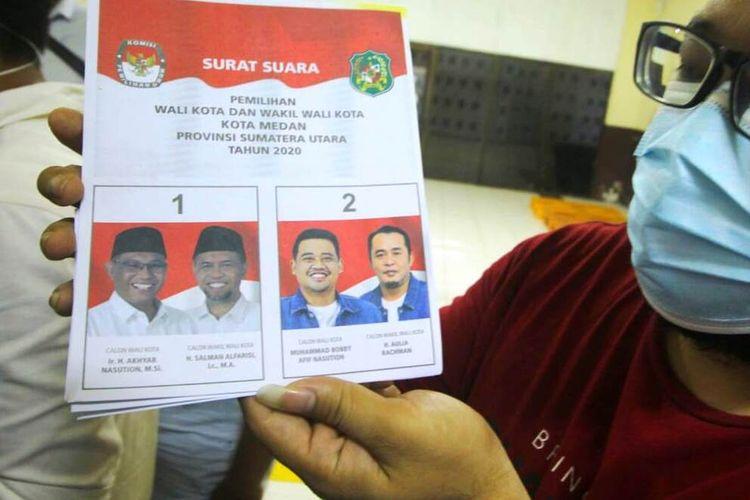 Seorang petugas sortir surat suara menunjukkan foto paslon wali kota dan wakil wali kota Medan nomor urut satu AMAN terlihat lebih gelap di banding foto paslon nomor urut dua, Kamis, (19/11/2020)