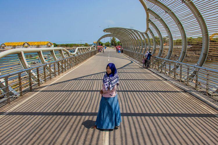 Seorang pengunjung berfoto di Jembatan Pantai Boom Banyuwangi.