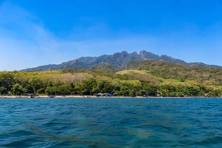 Lanskap Pantai Pasir Putih Situbondo dengan latar belakang pegunungan.