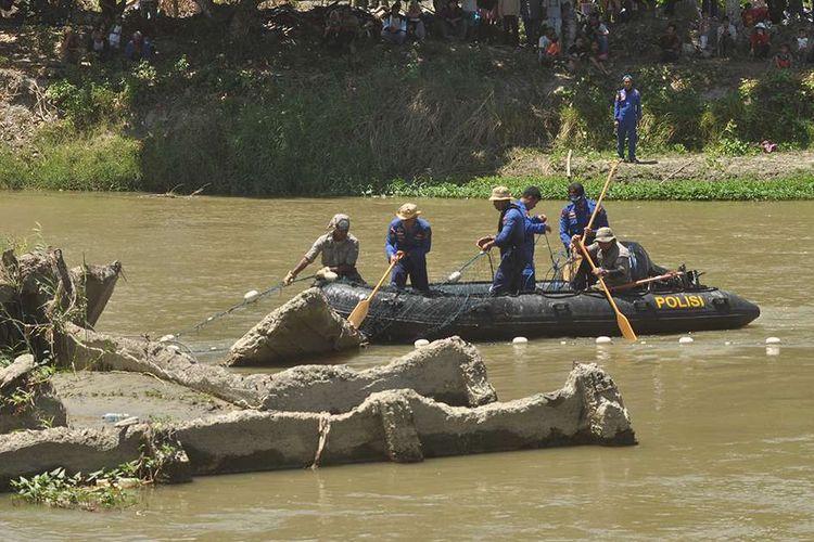 Petugas memasang jaring untuk mempersempit ruang gerak buaya liar yang terjerat ban sepeda motor saat berlangsungnya proses penyelamatan di Sungai Palu, Sulawesi Tengah, Jumat (7/2/2020). Perilaku buaya yang berpindah-pindah dan sulit didekati serta banyaknya warga yang berada dilokasi menjadi kendala utama yang dihadapi petugas untuk melakukan proses evakuasi dalam upaya penyelamatan satwa tersebut dan terpantau hingga pukul 18.00 WITA buaya tersebut belum berhasil ditangkap oleh petugas.