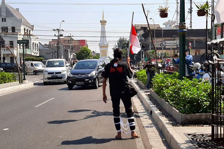 Aktivis anti korupsi Yogyakarta, Baharuddin Kamba saat melakukan aksi jalan mundur dari Tugu Yogyakarta. Aksi ini sebagai bentuk kekecewaan terhadap ditandatanganinya Supres revisi UU KPK, Jumat (13/9/2019).