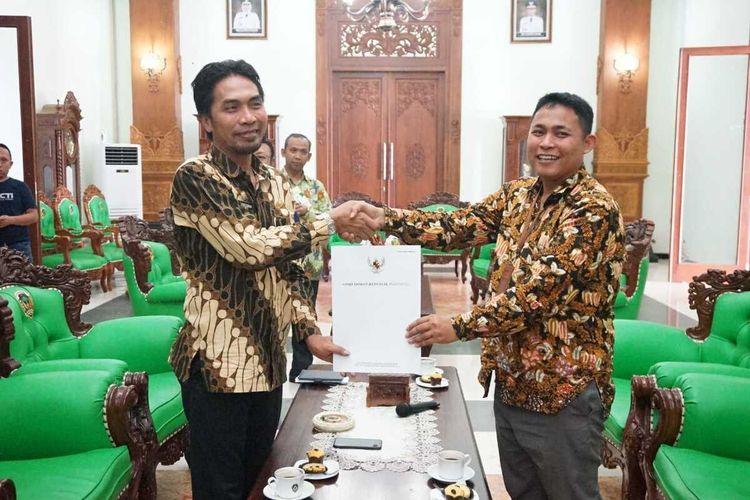 BERIKAN LAPORAN-- Asisten Bidang Pencegahan Ombudsman Jawa Timur, Mufihul Hadi (kanan) memberikan laporan penilaian terhadap standar pelayanan publik di Kabupaten Madiun dengan nilai hijau kepada Bupati Madiun, Ahmad Dawami, Selasa (21/1/2020)