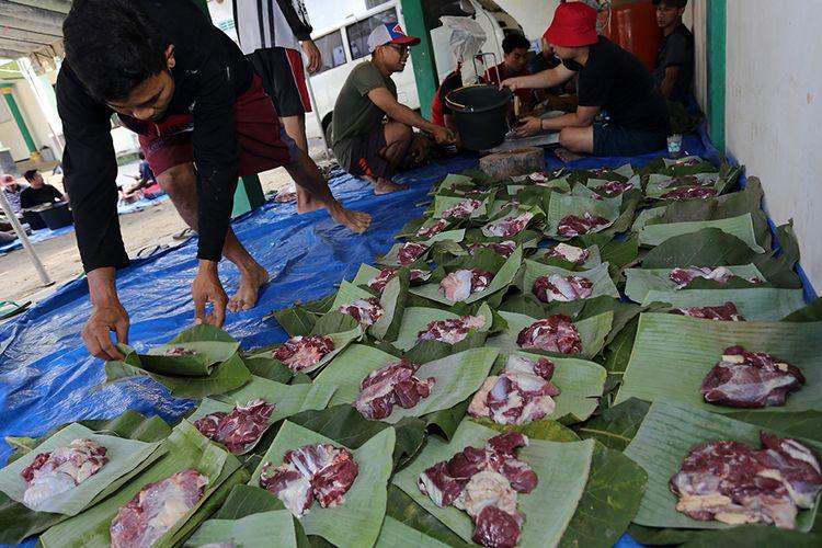 Warga menata daging kurban diatas daun pisang dan daun jati di Blitar, Jawa Timur, Minggu (11/8/2019). Sejumlah warga dan instansi didaerah tersebut memanfaatkan dedaunan dan wadah dari anyaman bambu (besek) untuk membungkus daging kurban yang bertujuan untuk mendukung program pemerintah dalam meminimalisir penggunaan plastik (diet plastik).