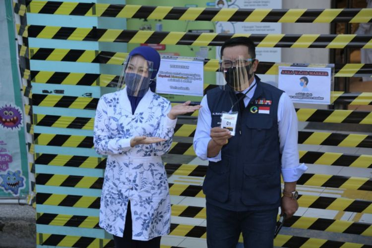 Gubernur Jawa Barat Ridwan Kamil diantar istrinya Atalia Praratya sebelum menjalani tahap pertama uji klinis vaksin Covid-19 di Puskesmas Garuda, Kota Bandung, Selasa (25/8/2020).