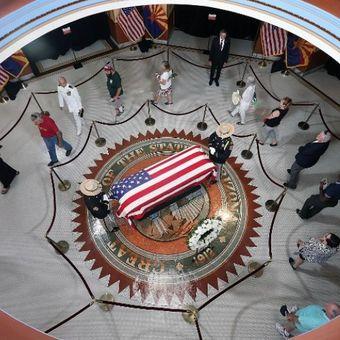 Masyarakat melihat peti mati Senator John McCain saat jenazahnya dibawa ke Arizona State Capitol Rotunda  pada Rabu (29/8/2018) di Phoenix, Arizona. (AFP)