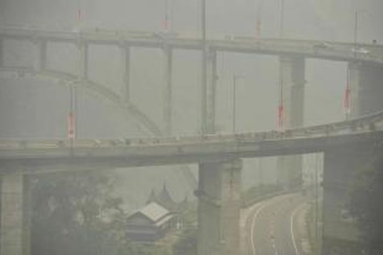Para pebalap menembus kabut asap saat melintas di Jembatan Kelok Sembilan, Kabupaten Lima Puluh Kota, Sumatera Barat, dalam etape kelima Tour de Singkarak, Rabu (7/10/2015).