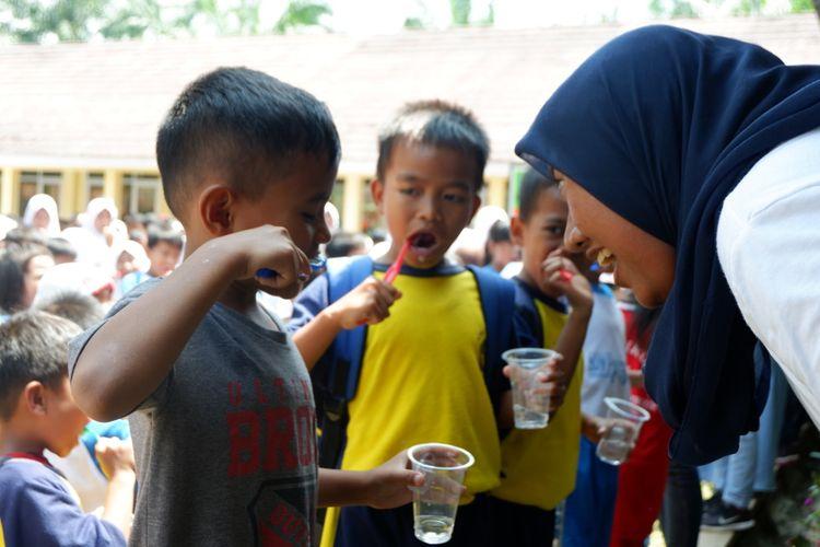 Seorang penerima beasiswa LPDP sedang mengajari anak menggosok gigi yang benar, di SD desa Cimulang, Bogor dalam program yang digelar APK ke-141 LPDP (30/3/2019).