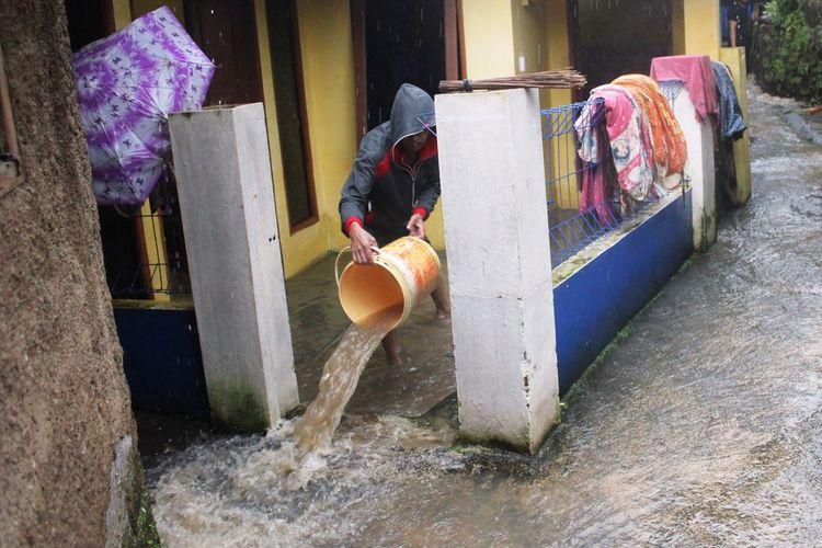 Seorang warga di Kampung Cikaret, Cianjur, Jawa Barat, membersihkan rumahnya dari air yang sempat merendam akibat banjir bandang, Selasa (21/5/2020)
